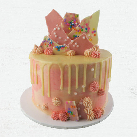 Pretty pink watercolour drip cake with a white chocolate ganache drip.