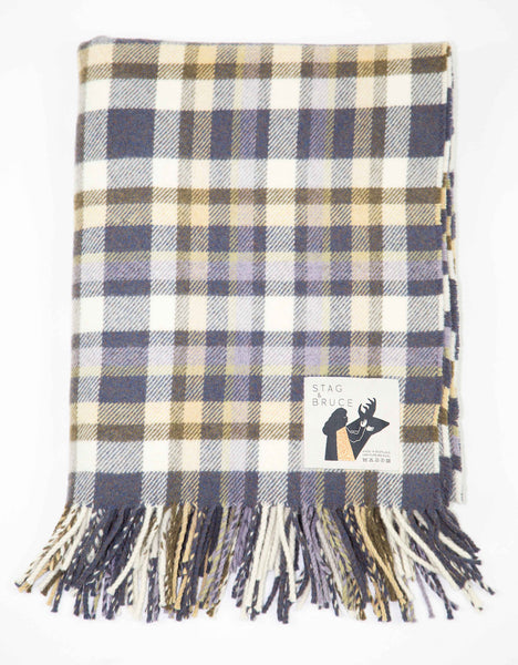 A wool throw with multi block check in grey, yellow and purple