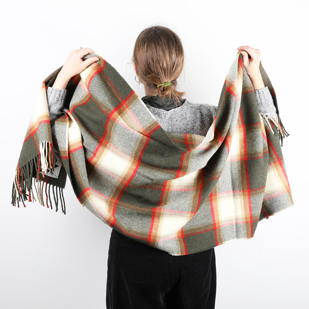 A wool shawl/stole featuring a country block check of forest green and brackens with ecru and a highlight of vermillion.