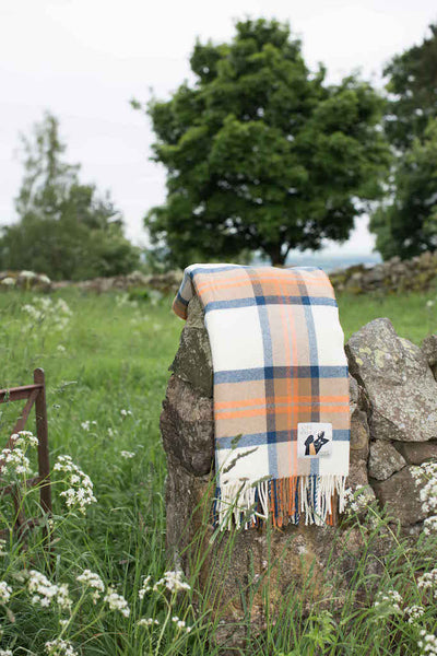 Wool throw in blue and orange check inspired by the Scottish landscape