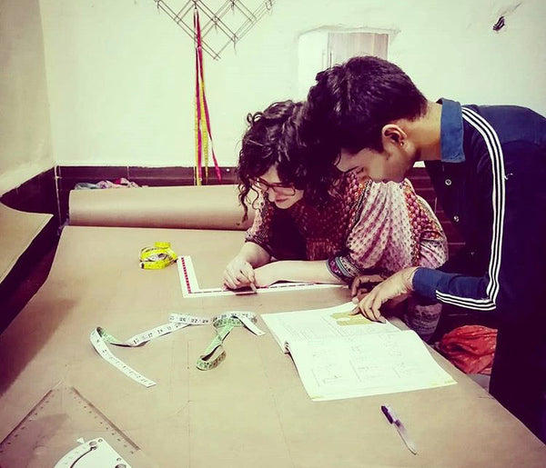 picture of a college volunteer drafting sewing patterns with Sewing New Futures Staff member in New Delhi India