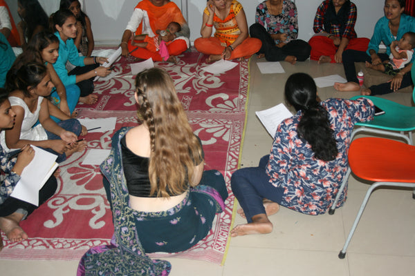Group of Indian women with college volunteer at the sewing new futures center in New Delhi
