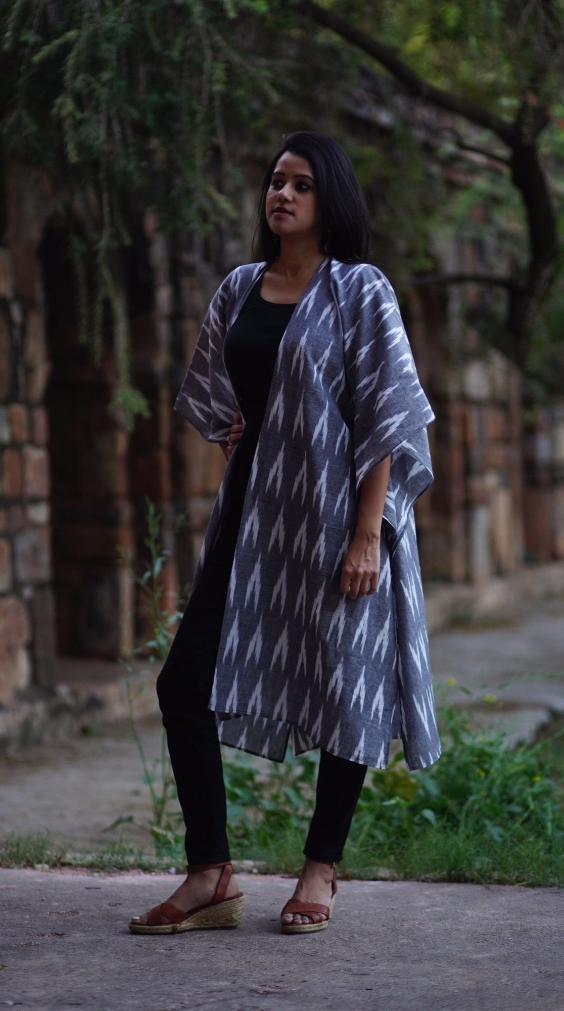 woman wearing a grey ikat kimono shrug sustainably sewn by sewing new futures NGO