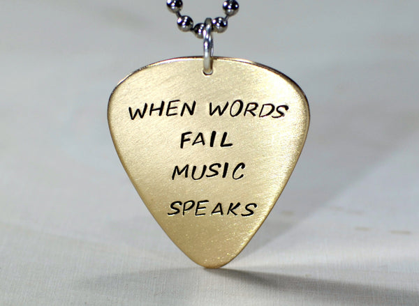 Bronze guitar pick pendant handmade with When words fail music speaks