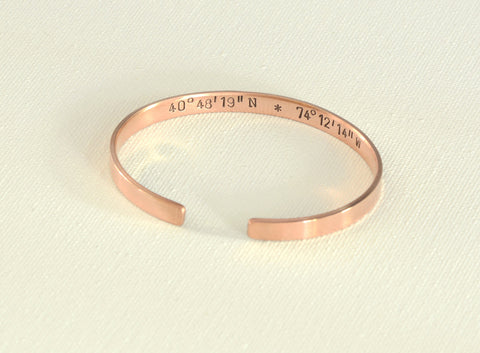 Latitude longitude coordinates stamped on the inside of a polished copper bracelet