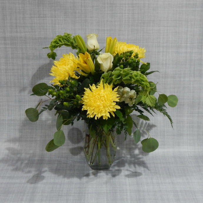 Bright yellow mums and lilies, with bells of ireland, and white roses in tall vase