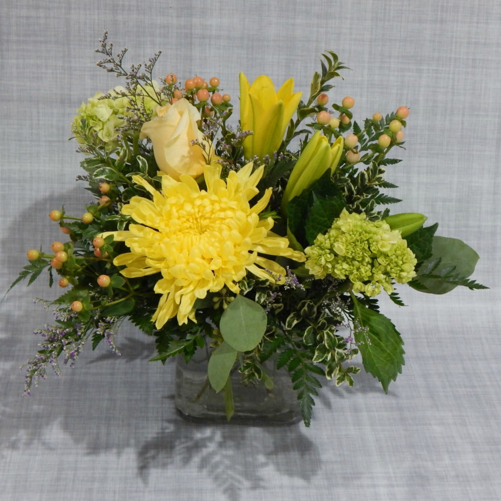 Bright yellow  lilies, roses and mums with  green hydrangeas