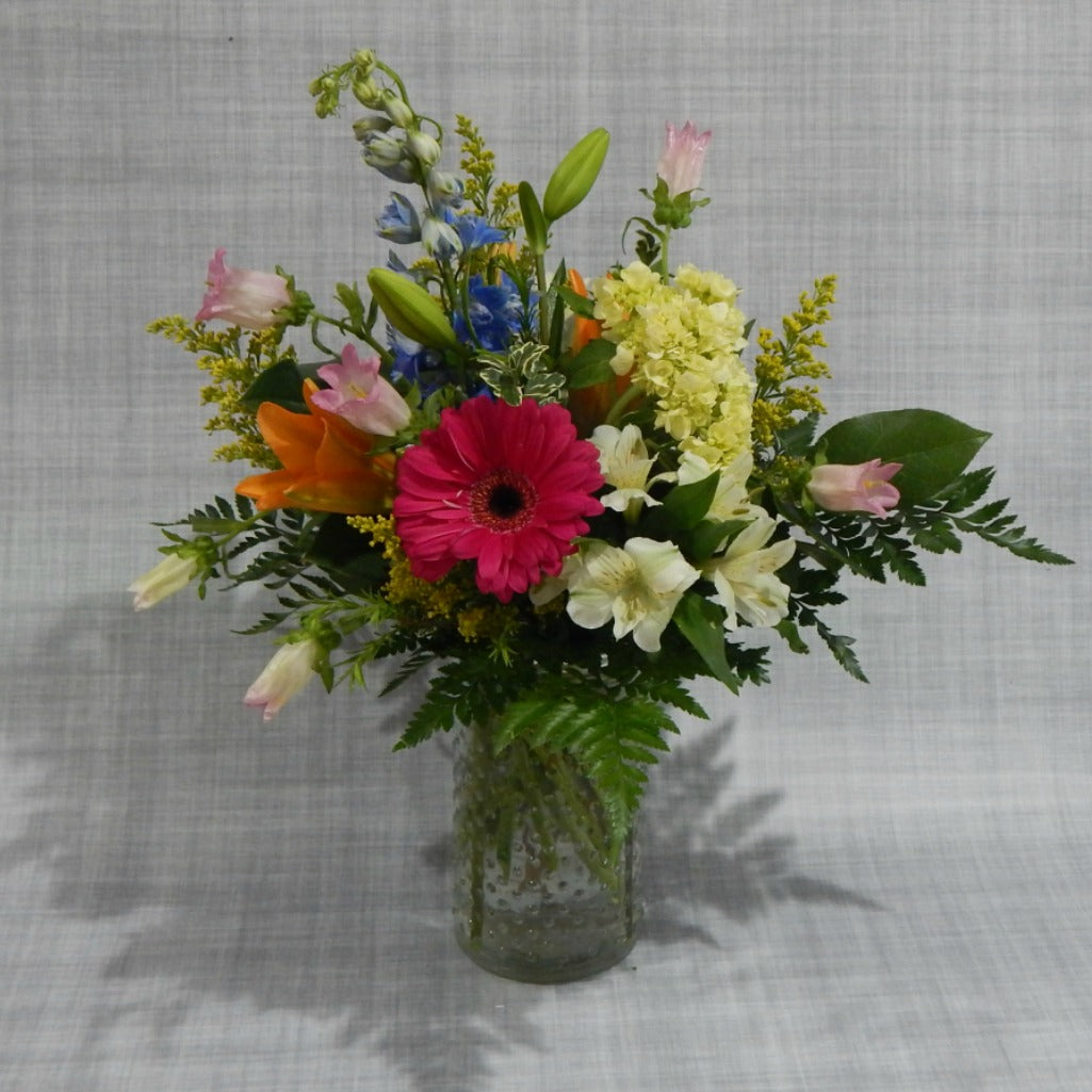 Cheery flower arrangement of bright colors, with a fresh from garden feel