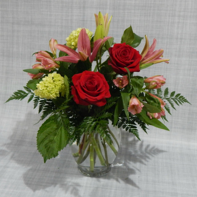 Colorful vase arrangement of pink lilies, red roses and green hydrangeas- perfect thinking of you flowers.