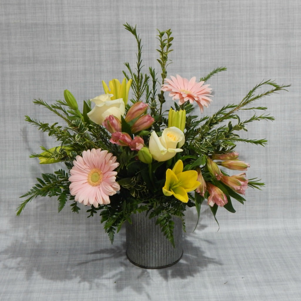 Pink & yellow  garden flowers arranged in a rustic tin vase