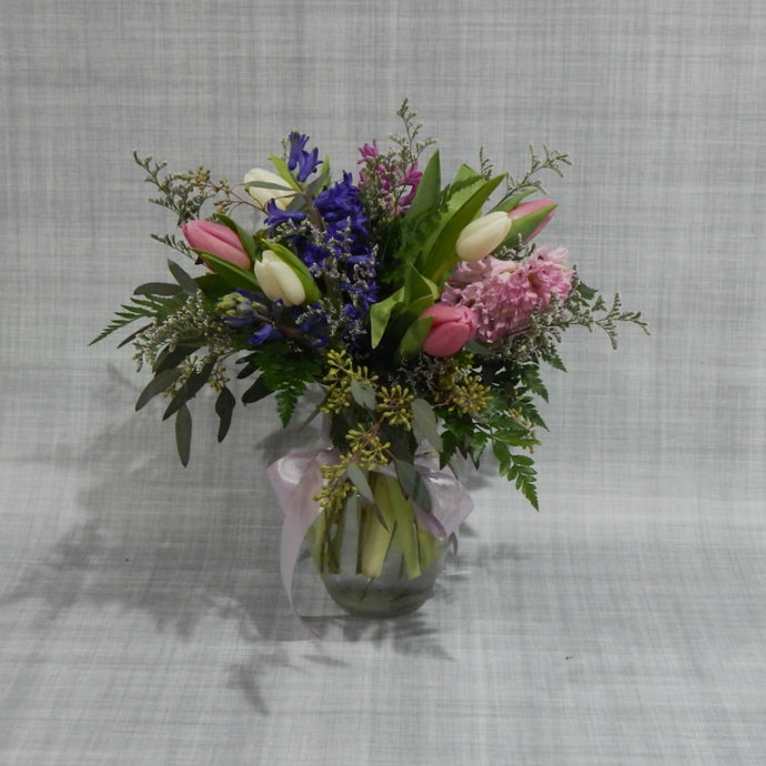 Spring tulips and hyacinths in glass vase with pretty garden greens and heather