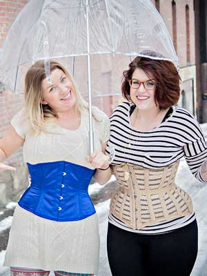 friends side by side sharing an umbrella, one in the blue satin Modern Curve Underbust Corset CS-411 and the other in a beige mesh Hourglass Curve Longline Underbust Corset CS-426