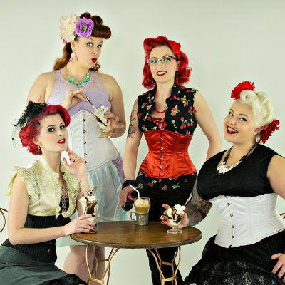 retro group of four woman in corsets at an old-fashioned soda fountain