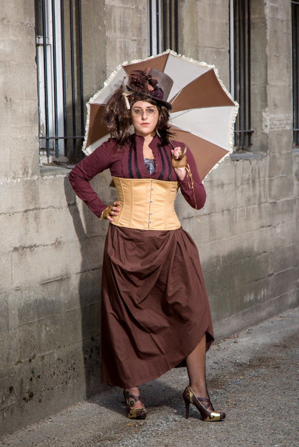 Woman dressed in steampunk clothing wearing a beige underbust corset with umbrella
