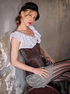 woman in satin corset style CS-426 longline with back against train tunnel