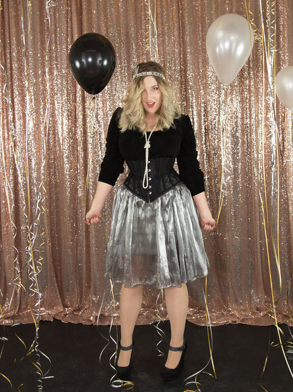 Model wearing our cs 201 black lace underbust waist training corset with a silver skirt holding balloons