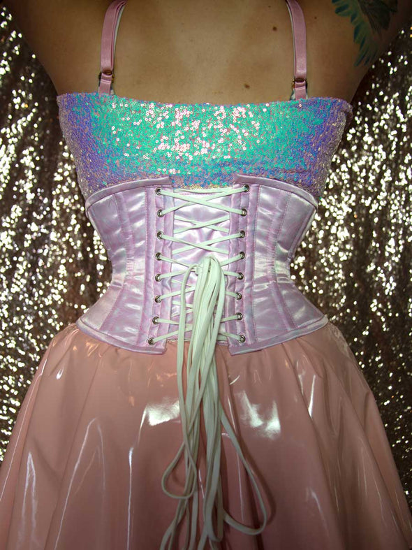 Back lace up view of a Model in holographic skates wearing a pink PVC skirt and irridescent top with the limited edition pink galaxy cs201 hourglass curve corset