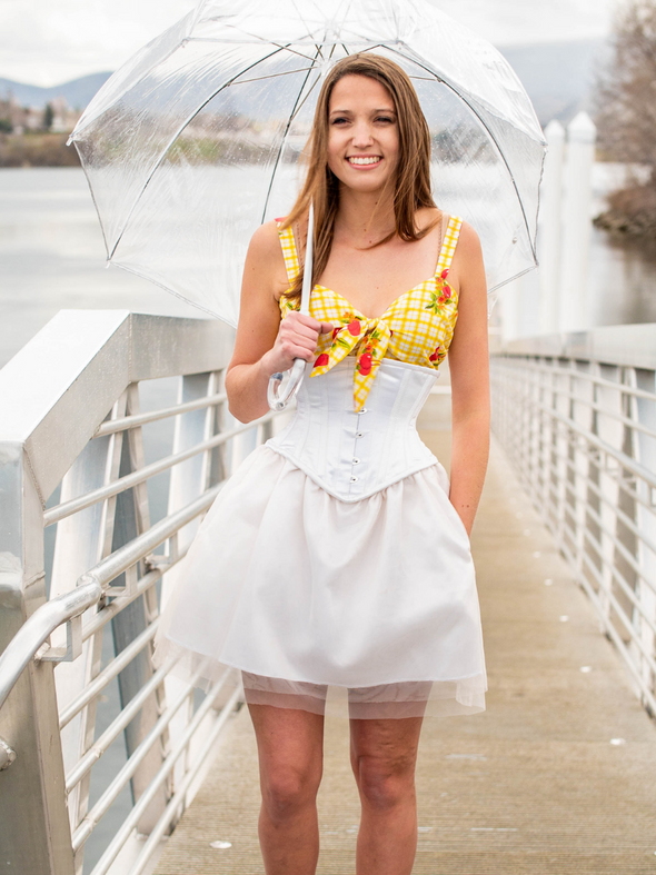 model under an umbrella wearing a yellow top with a cs 201 ivory satin steel boned corset dress with tulle skirt