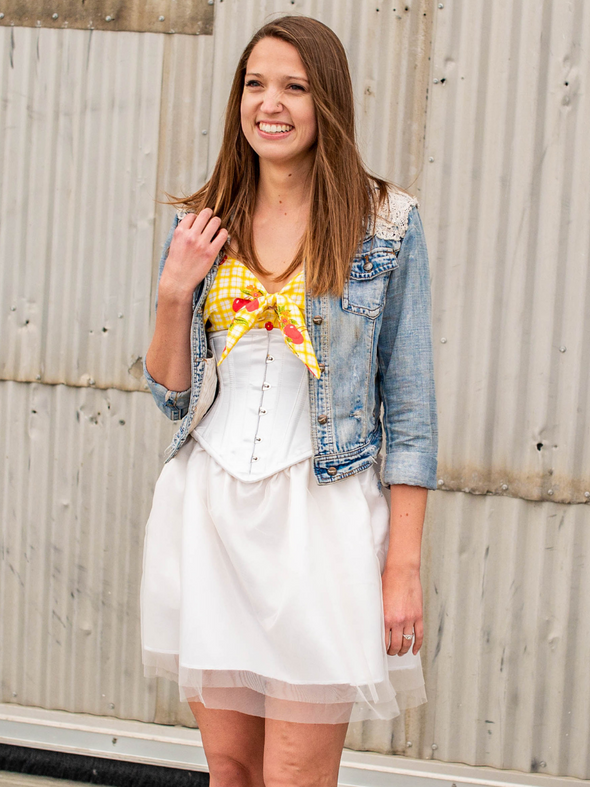 model wearing a yellow top and denim jacket with a cs 201 ivory satin steel boned corset dress with tulle skirt