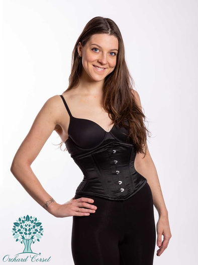 smiling model wearing the romantic curve cs219 in black satin waist training corset with hand on her hip