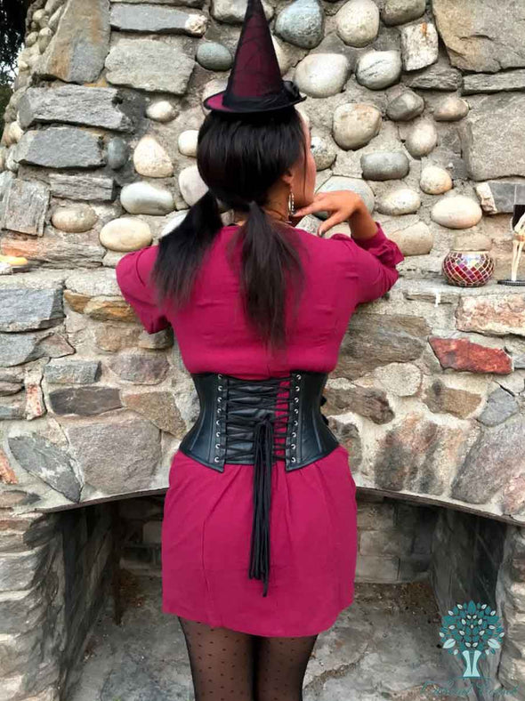 cs301 back lace up view of this black leather corset with fashion accents model in a red dress leaning on a rock fireplace