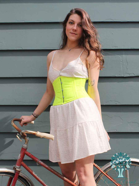 model in sundress posing with a bicycle in a cs301 modern curve silhouette in NEON yellow green cotton waist trainer corset