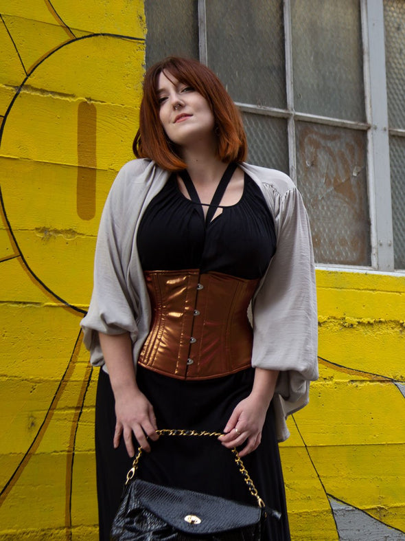 Model with shoulder length red hair wearing a shimmering duotone red gold romantic curve waist training corset