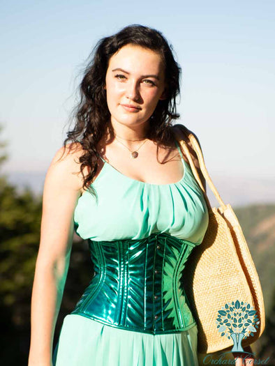 cs411 metallic pvc waist trainer shown on brunette model  with blue sky backgraound