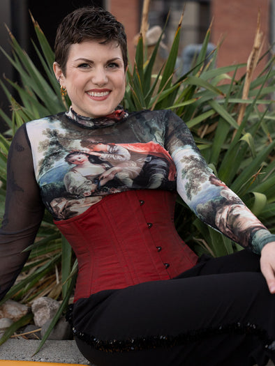 Female model sitting, wearing the CS411 standard waist training corset in crimson red shantung over a mesh print shirt and black tuxedo pants