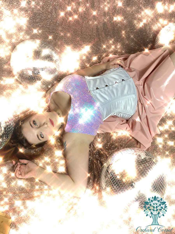 woman modeling a white satin romantic curve cs411 standard corset with pink latex skirt and irridescent strap blouse.  Laying on sequins with disco balls