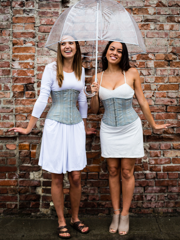 2 models wearing our 411 gray plaid cotton corsets one in the standard length one in the longline length