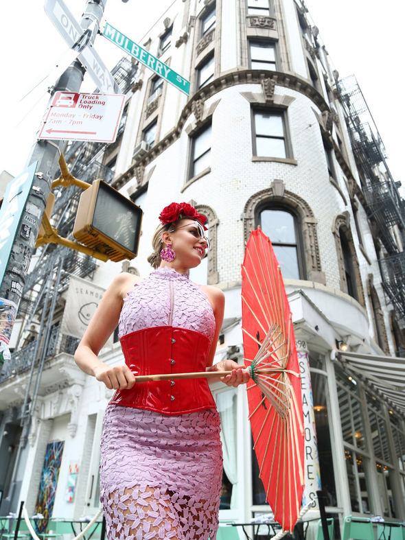 Model wearing our cs 411 standard underbust PVC corset in red holding an umbrella