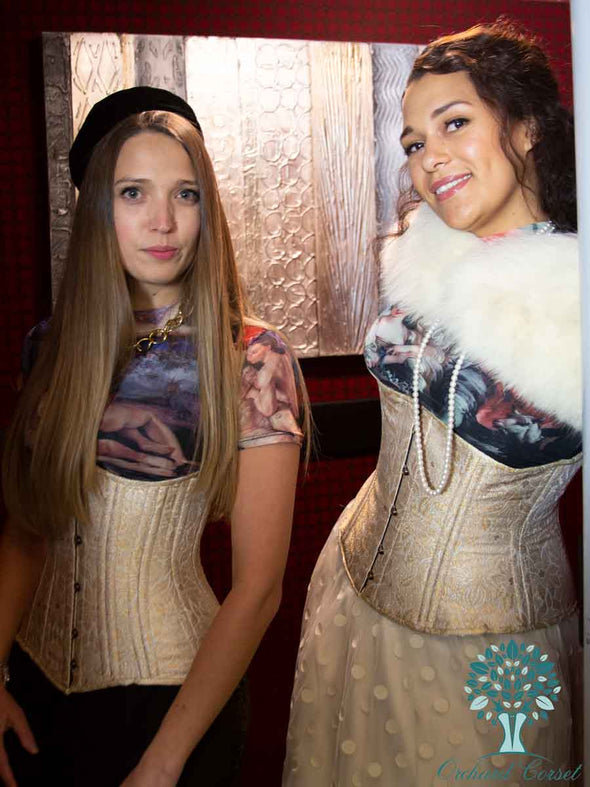 two models wearing gold brocade corsets in style cs411 longline and cs426 longline riding a red elevator