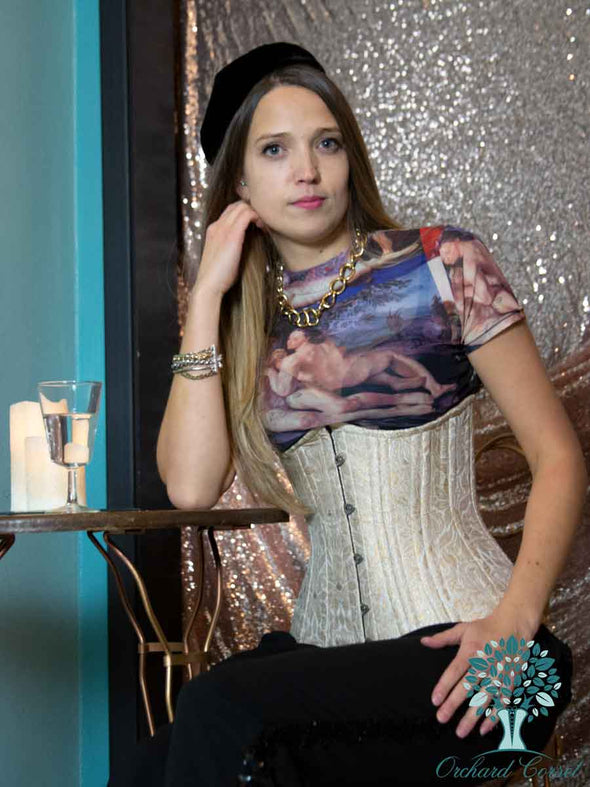 Model wearing cs426 longline gold brocade waist training corset in bistro setting