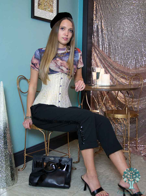 Model wearing cs426 longline gold brocade waist training corset in bistro setting with black beret, purse and shoes