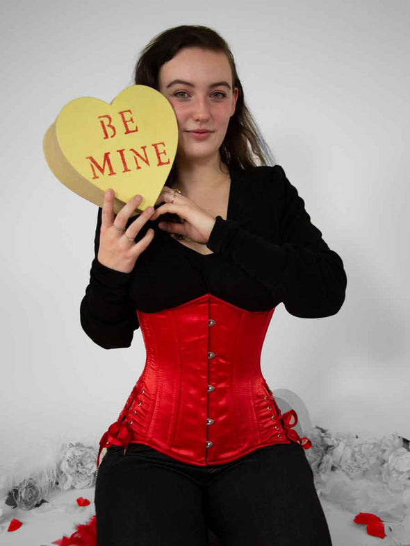 Model holding valentine's conversation heart and wearing the 426 longline with hip ties in rich red satin underbust corset top