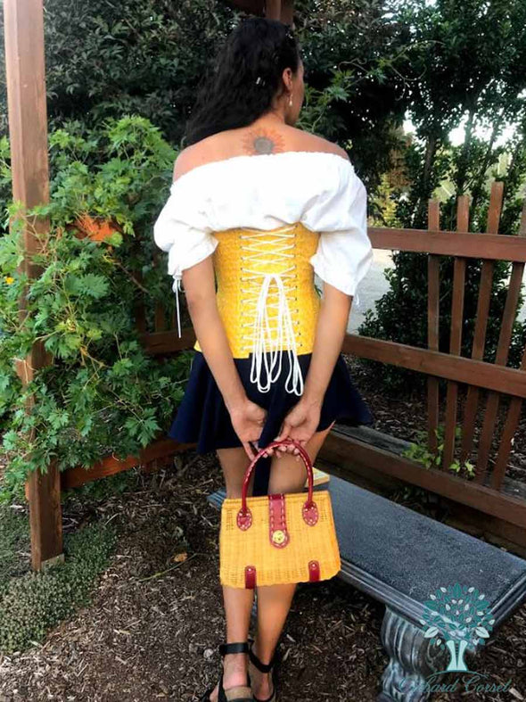 Back lace up view showing white lacing on a OC hourglass curve 426 longline corset in a lovely cotton saffron eyelet fabric over a white blouse and black skirt with a yellow and red straw purse