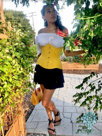 Model wearing OC hourglass curve 426 longline corset in a lovely cotton saffron eyelet fabric with a white top and black skirt gazing at flowers