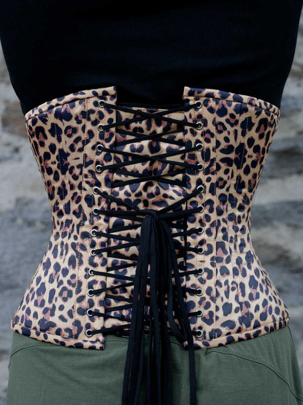back lace up view of cs426 hourglass curve waist training corset in leopard print worn by model sporting a leather moto styled jacket and black boots
