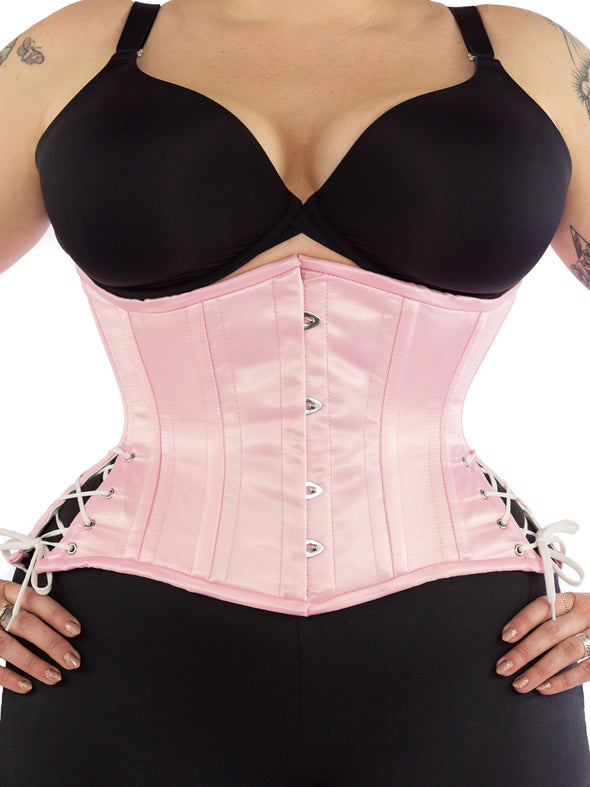 Model wearing our plus size 426 with hip ties steel boned waist training corset in pink satin