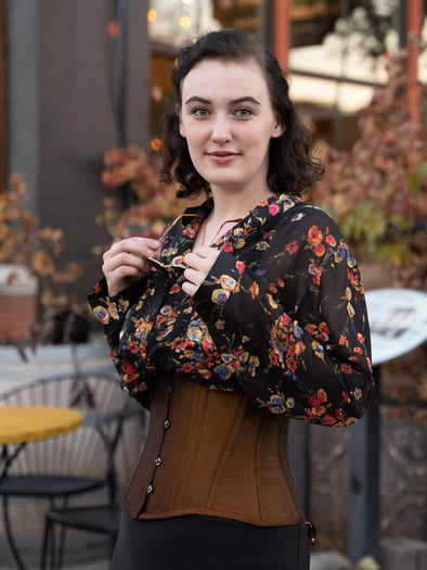 Black Friday special sale cs 426 standard waist training corset in premium bronze shantung fabric shown on model wearing a black floral print blouse and black skirt at a restaurant