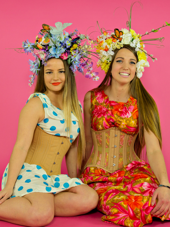 Model in a polka dot dress and floral head dress wearing a cs 426 standard in beige cotton sitting next to a model wearing a floral print dress and floral head dress in a cs 426 standard beige mesh steel boned corset