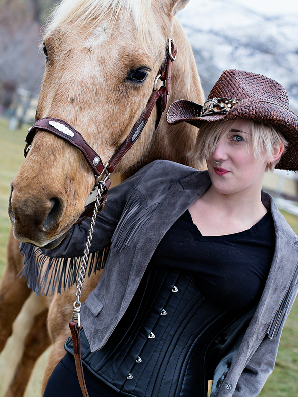 Model walking a horse wearing our underbust 426 longline steel boned black leather corset tops