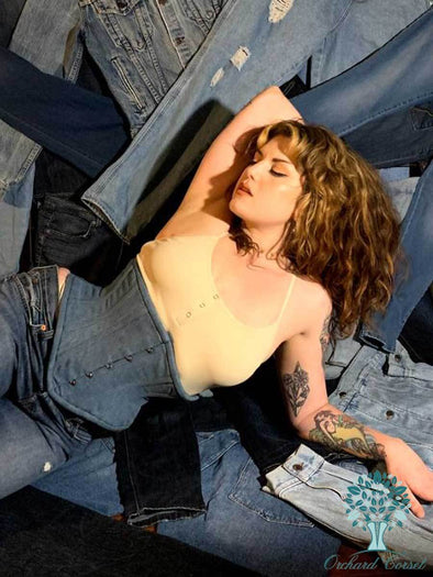Model lounging wearing May Limited edition hourglass curve denim 201 waspie with contrasting stitching
