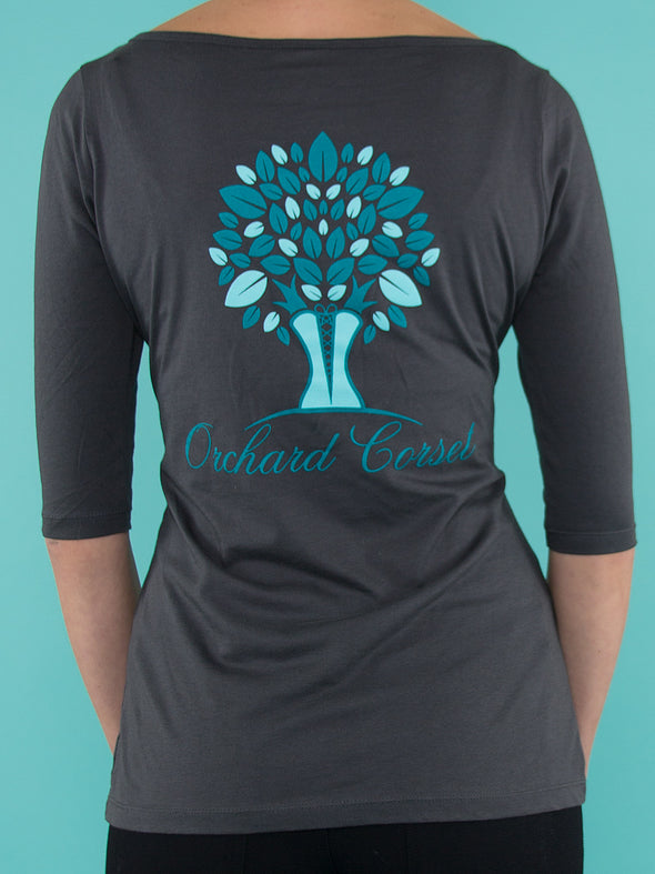 back facing model wearing gray orchard corset logo t-shirt