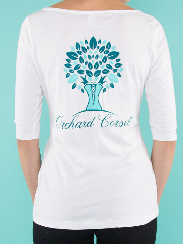 back facing model wearing white orchard corset logo t-shirt