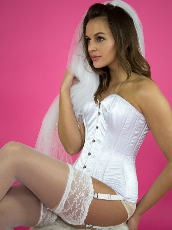 Model wearing white corset, stockings, and white garter extensions.