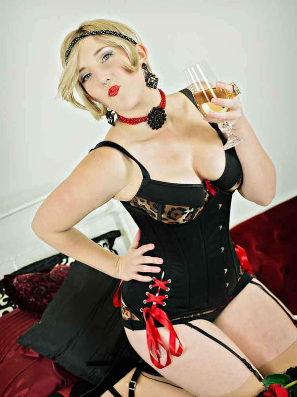 Model in garters and stockings wearing 426 longline corset with hip ties and red laces