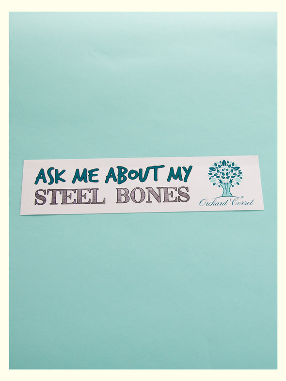 "Bumper sticker reading ""ask me about my steel bones"" with Orchard Corset logo"
