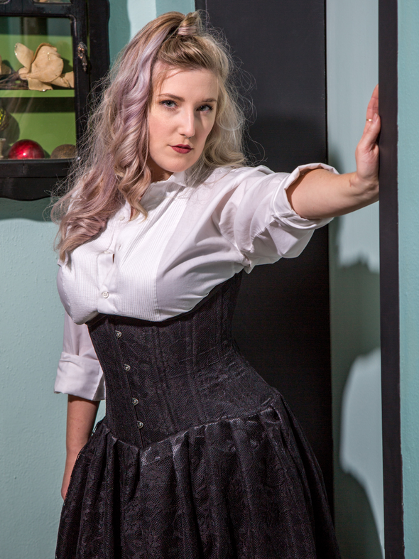 model in a white button up shirt wearing our underbust 426 corset dress in black satin and lace